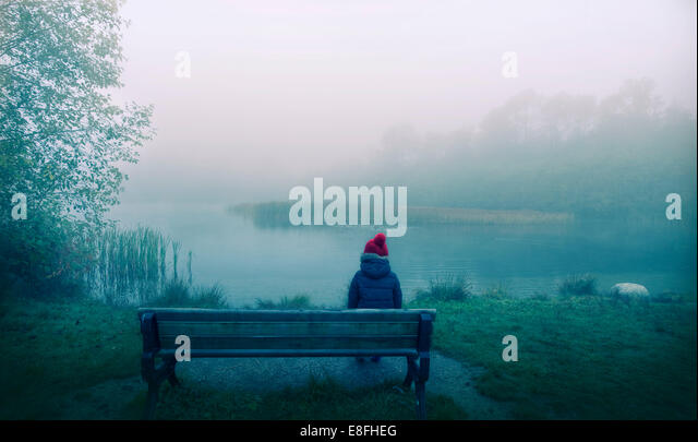 Canada, British Columbia, Greater Vancouver Regional District, Vancouver, Boy sitting on bench - Stock Image