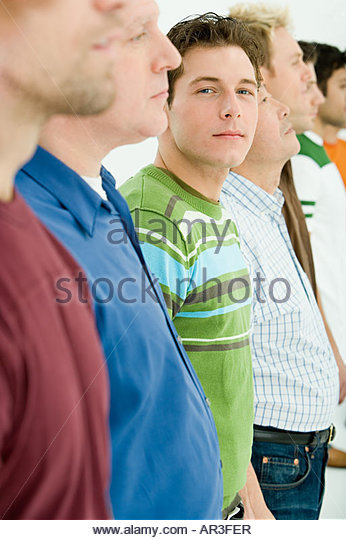 Young man looking out from row of men - Stock Image