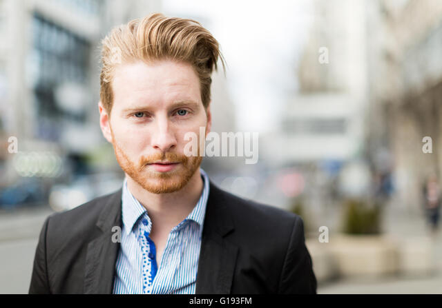 Businessman portrait with blurred out city buildings in the background - Stock Image