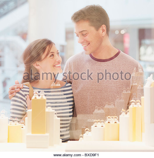 Smiling couple looking at jewelry in display case - Stock-Bilder