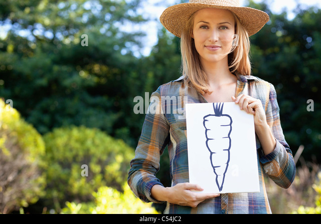 Portrait of a young woman showing carrot painting in a field - Stock Image