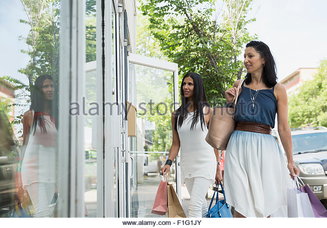 Women window shopping at storefront - Stock Image