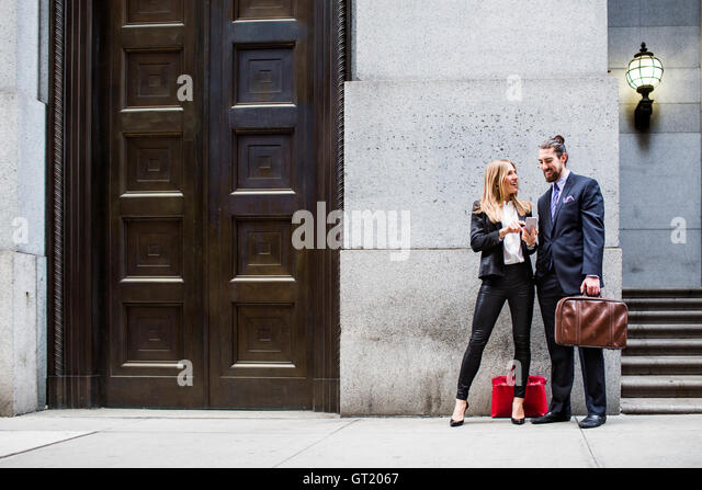 Businessman and woman looking at smart phone while standing on sidewalk - Stock-Bilder