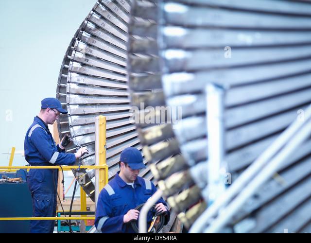 Engineers repairing steam turbine in repair bay in workshop - Stock Image