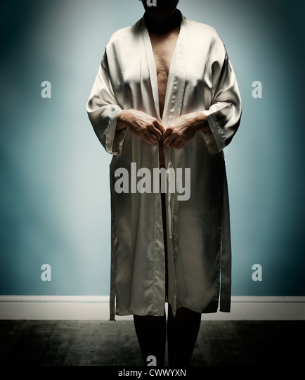 Older woman wearing open bathrobe - Stock Image