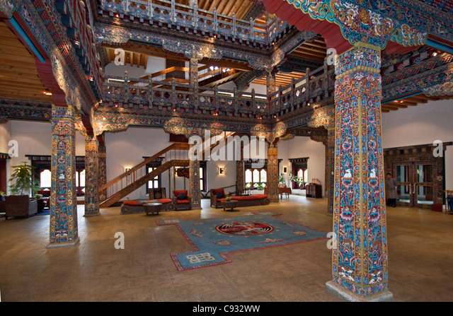 The ornate entrance hall of the grand Zhiwa Ling luxury hotel, eight km from Paro in the Paro Valley. - Stock Image