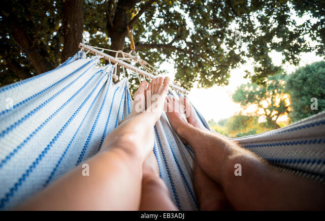 Couple relaxing in hammock under tree - Stock Image
