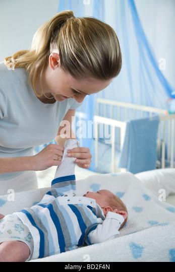 mum dressing up infant - Stock Image