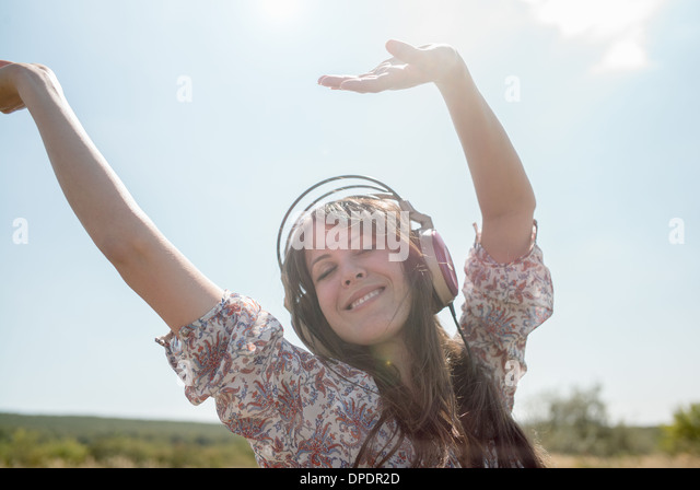 Portrait of mid adult woman dancing in field wearing headphones with arms raised - Stock Image