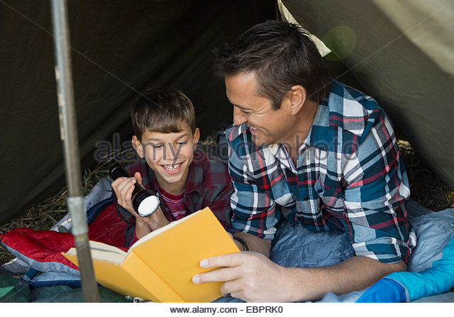 Father and son reading book inside tent - Stock Image