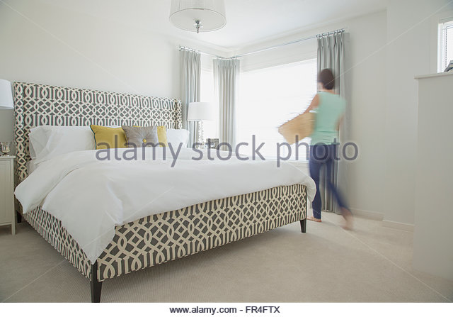 Woman with laundry basket in contemporary bedroom. - Stock-Bilder
