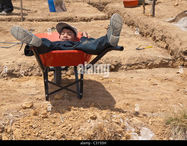 A young Guatemalan boy pretends to sleep in a wheelbarrow at a work site for the construction of a new house in - Stock Image