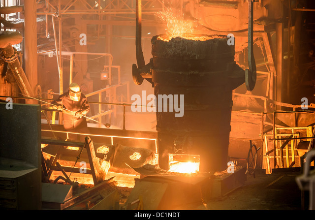 Elevated view of steel worker and molten bucket in steel foundry - Stock Image