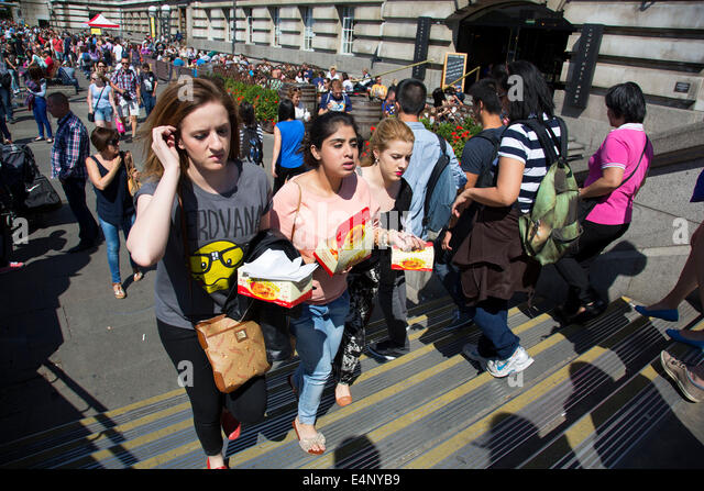 Girls climb the steps holding boxes of fast food. South Bank, London, UK. - Stock Image