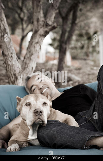 Dog Whisperer Ceasr Millan at ranch shows love and affection laying down relaxing with pitbull dog Daddy on big - Stock Image