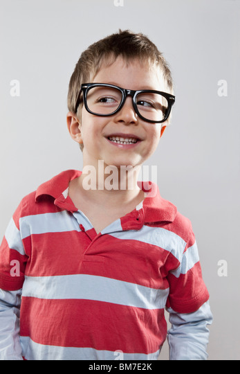 A young boy wearing fake glasses and smiling slyly, studio shot - Stock Image