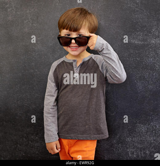 Portrait of happy little boy wearing sunglasses smiling at camera. Small boy peering over his sunglasses against - Stock Image