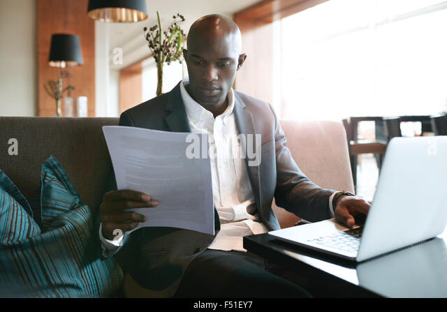 Image of young businessman sitting a hotel coffee shop reading a document while working on laptop. Preparing himself - Stock Image