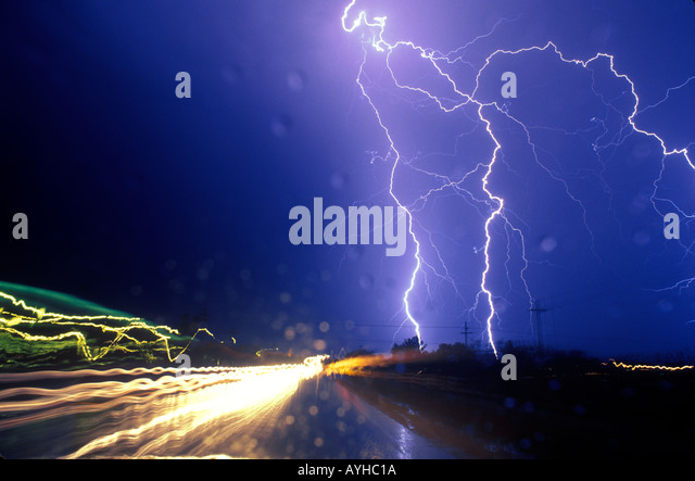 Lightning strikes near a road with car headlights blurring by. Water droplets on the windshield play in the foreground. - Stock Image
