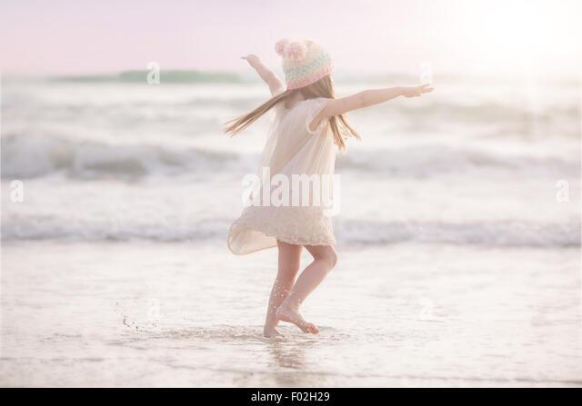 Girl dancing on the beach - Stock Image