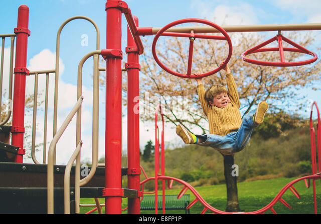 Boy  (4-5) hanging from playground climbing frame and  laughing - Stock Image
