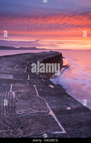Spectacular winter sunrise above The Cobb harbour wall, Lyme Regis, Dorset, England. Winter (February) 2013. - Stock Image