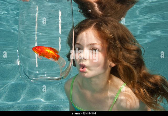 swimming underwater in swimming pool looking at goldfish in glass bowl - Stock Image