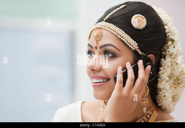 Bride in traditional South Indian dress talking on a mobile phone - Stock-Bilder