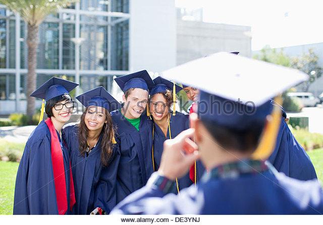 Graduate taking photograph - Stock Image