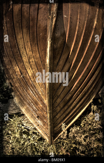 An upturned wooden rowing boat with brass fittings - Stock Image