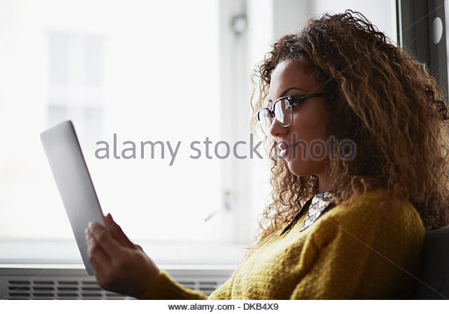Female office worker using digital tablet - Stock Image
