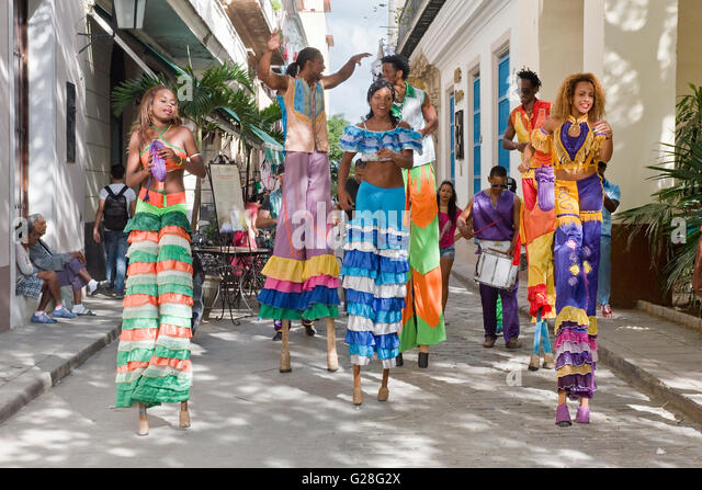 A group of stilt dancers entertaining locals and tourists in the Old Town of Havana collecting whatever money is - Stock Image