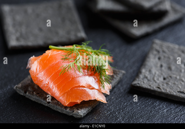 Smoked Salmon on black cracker - Stock Image