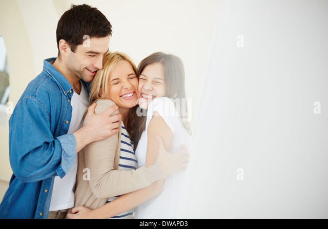 Portrait of joyful family of three in embrace - Stock Image