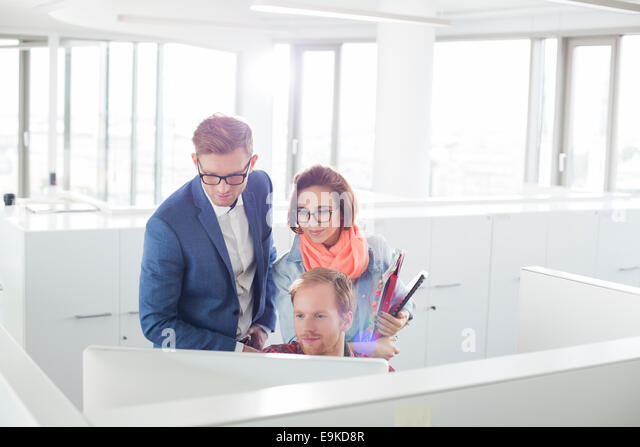 Business people working on computer in creative office - Stock Image