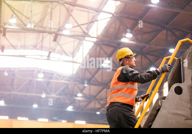 Steel worker climbing ladder in factory - Stock Image