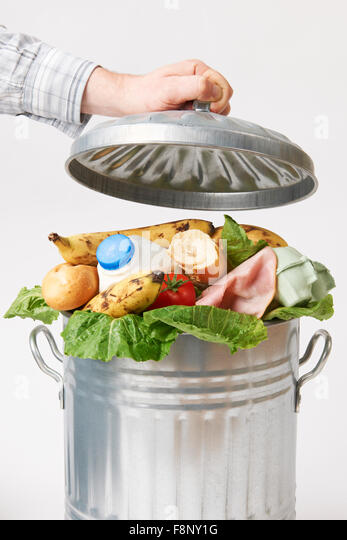 Hand Putting Lid On Garbage Can Full Of Waste Food - Stock Image