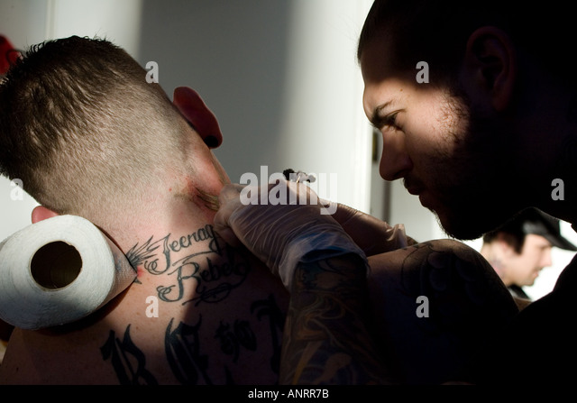 Young man getting a tattoo on his neck, London UK - Stock-Bilder