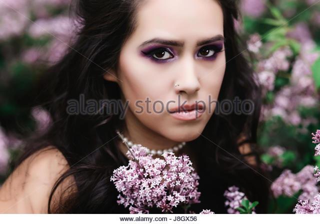 Brunette woman in lilac bush - Stock Image