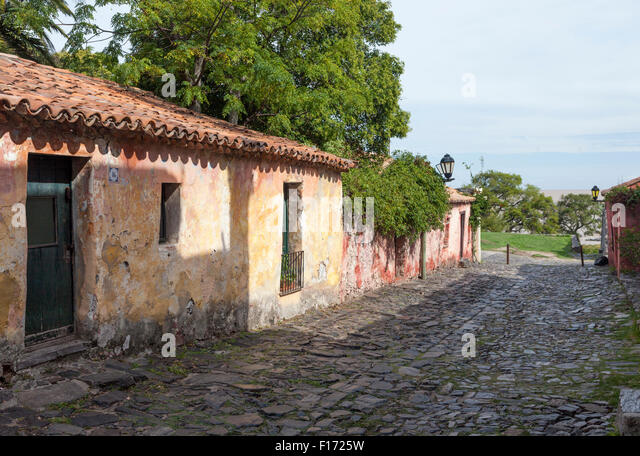 Red tile roofed stucco cottages on stone paved street in Colonia del Sacramento, Uruguay. The River Plate is visible - Stock Image