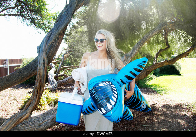 Young woman carrying cool box and inflatable tiger shark, Melbourne, Victoria, Australia - Stock-Bilder