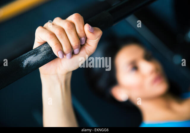 Young fit woman working out with barbell on bench. Focus on barbell - Stock-Bilder