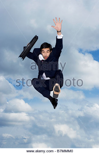 A businessman holding a briefcase, leaping in the air - Stock Image