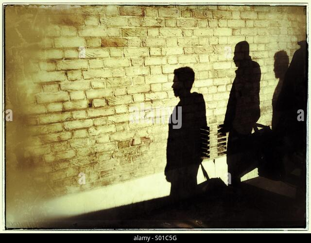 Shadows of three people on brick wall,Shoreditch,London ,UK - Stock-Bilder
