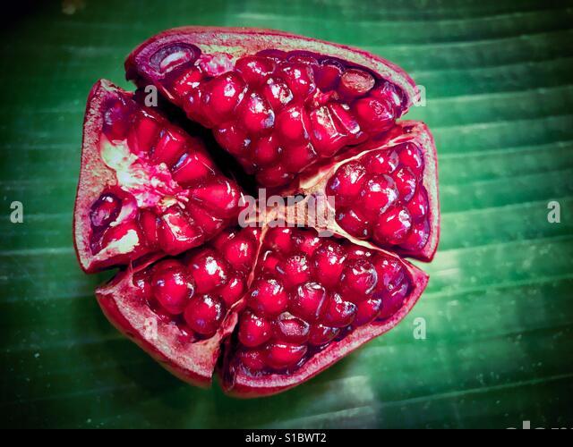 Red ripe pomegranate, (Punica granatum) on banana leaf background - Stock-Bilder