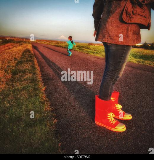 A mom wearing red boots watches while her little boy runs away on the path in the late afternoon. - Stock Image