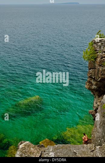 Mid adult woman crouching on rocks at coast, Toronto, Ontario, Canada - Stock Image