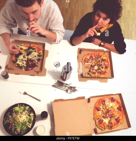 Overhead View Of People Having Pizzas At Table - Stock Image