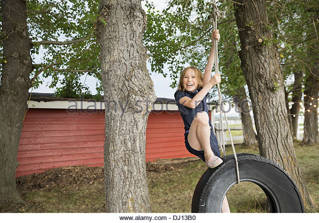 Happy girl playing on tire swing outdoors - Stock Image