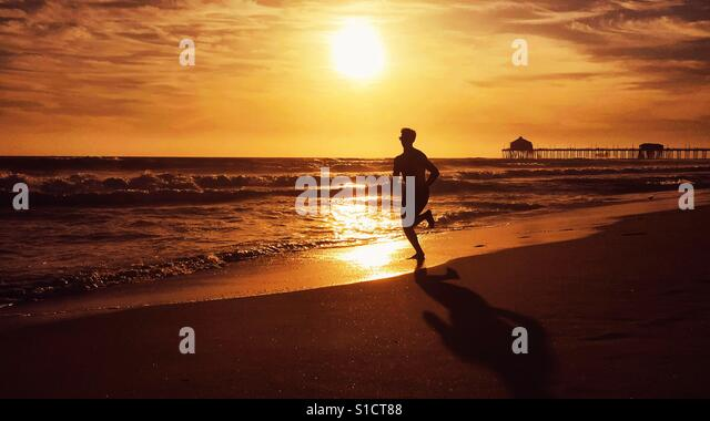 Young man running on the beach at sunset in California. - Stock-Bilder